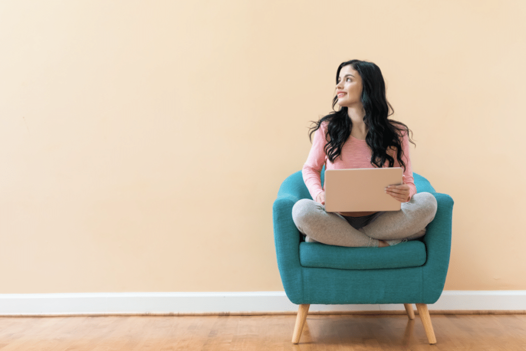 female student sitting on lounge with laptop
